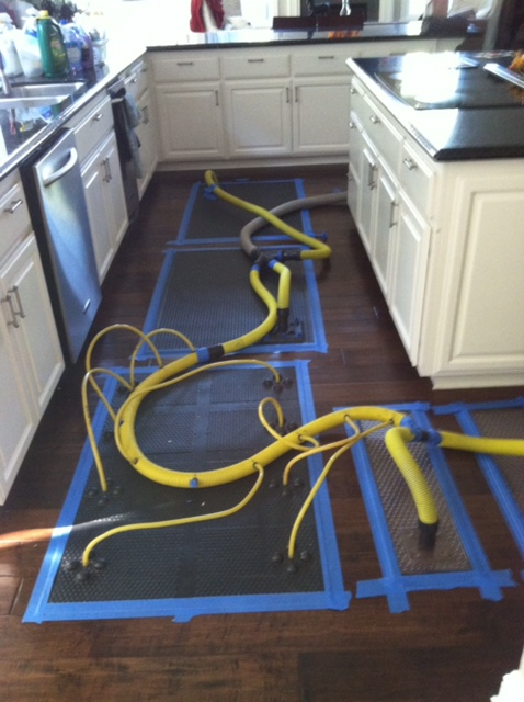 Yellow pipes with blue painters tape squares on hardwood floors in kitchen