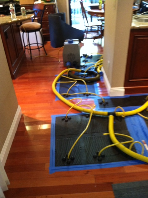 Yellow pipes with blue painters tape squares on hardwood floors with beige walls